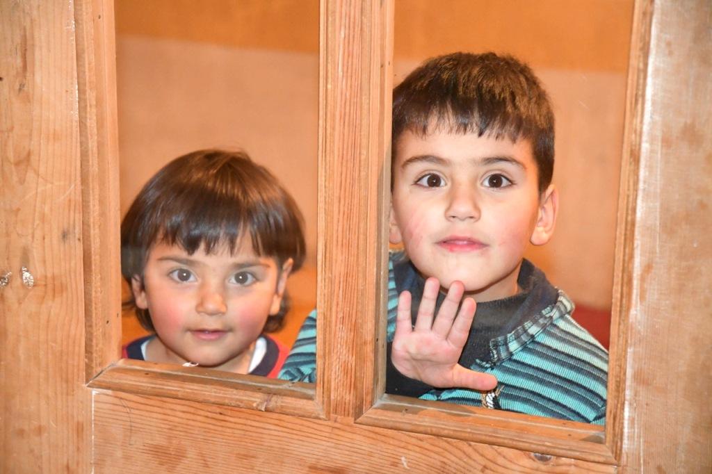 Zwei Kinder schauen durch die Glasscheibe einer Tür