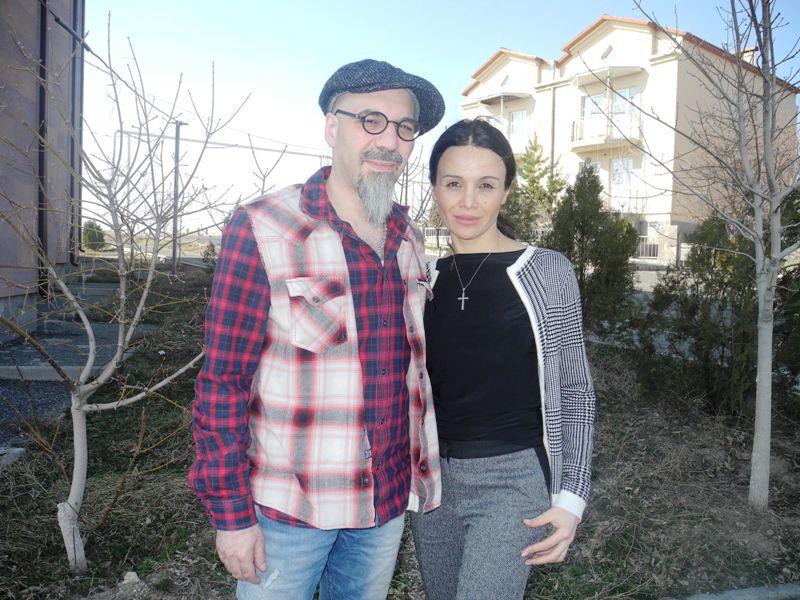 Baru und Anna Jambanzian stehen auf einem Rasengrundstück mit Bäumen; im Hintergrund sieht man ein Doppelhaus