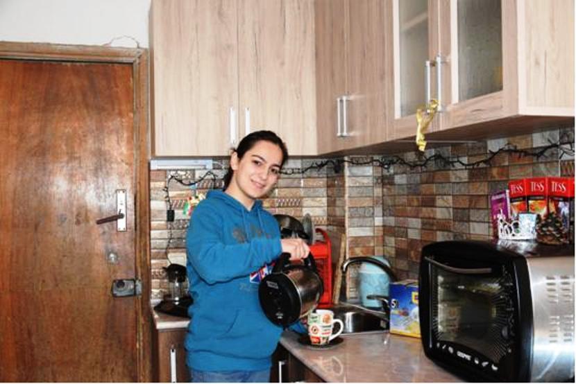 Junge Frau gießt in einer Küche Tee in eine Tasse