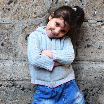 Dunkelhaariges Mädchen in hellblauem Pulli und mittelblauer Jeans steht mit verschränkten Armen lächelnd vor einer Mauer
