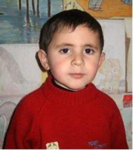 Kleiner Junge in rotem Pulli vor einer Wand mit Kinderzeichnungen