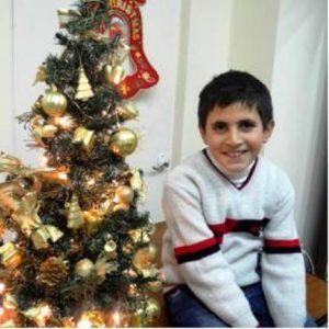 Junge in weißem Pulli sitzt neben einem Weihnachtsbaum