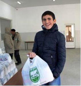 Älterer Junge in dunkelblauer Winterjacke hält eine Tüte mit Lebensmitteln