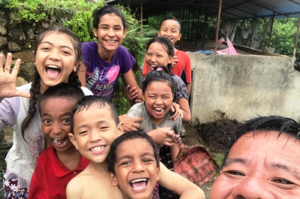 Acht Kinder schauen lachend in die Kamera