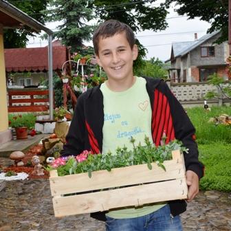Dunkelblonder Junge trägt eine Holzkiste mit Pflanzen und lächelt
