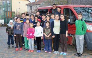 Kinder und Jugendliche stehen vor einem roten Transporter