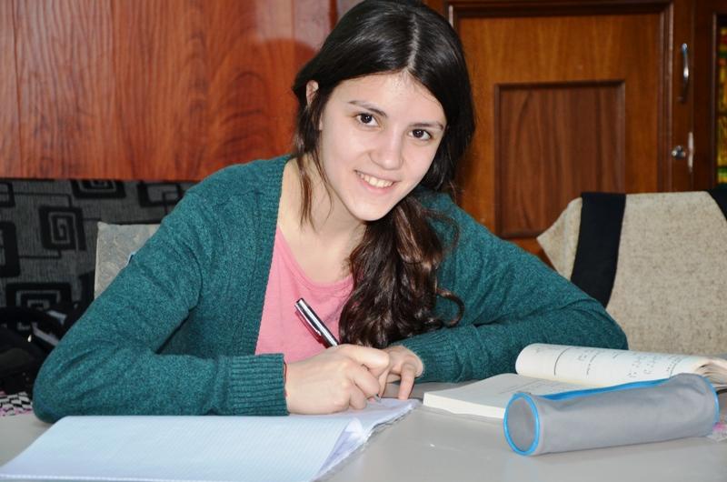 Junge Frau sitzt am Schreibtisch und schreibt