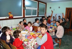 Kinder und Jugendliche sitzen an drei Esstischen