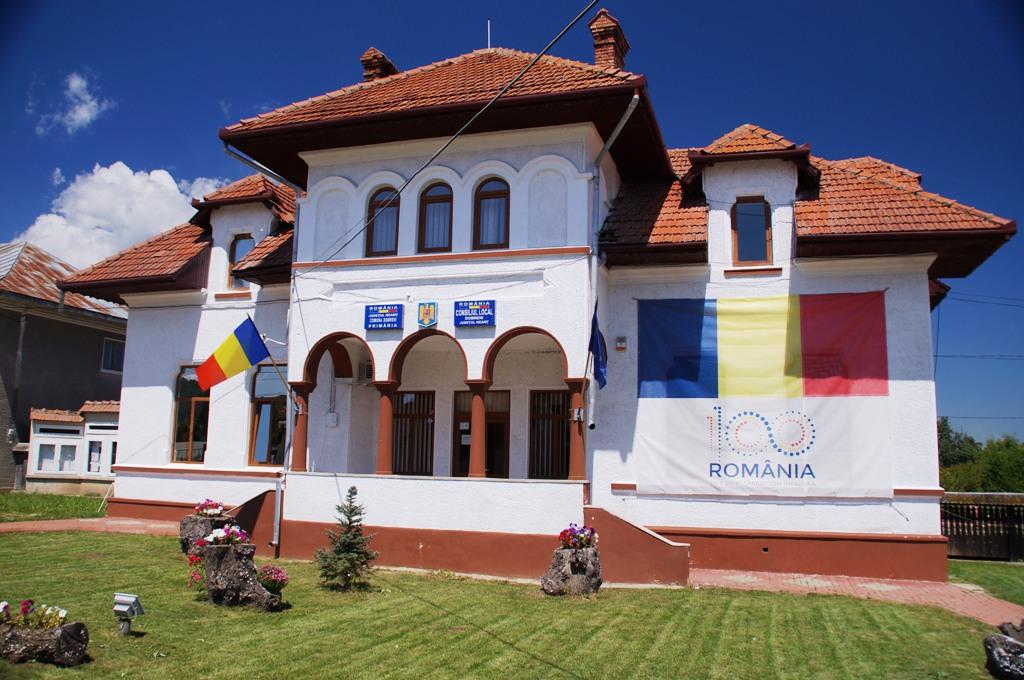 Helles zweistöckiges Gebäude mit rotem Dach, geschmückt mit rumänischen Fahnen