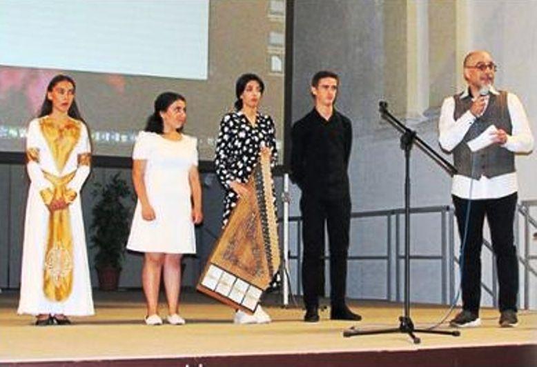 Vier Jugendliche - eines der Mädchen hält ein Instrument - stehen in einer Reihe; rechts ein Mann mit einem Mikrofon