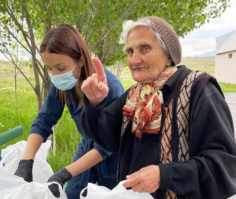 Eine alte Frau und eine jüngere Frau hantieren mit Tüten