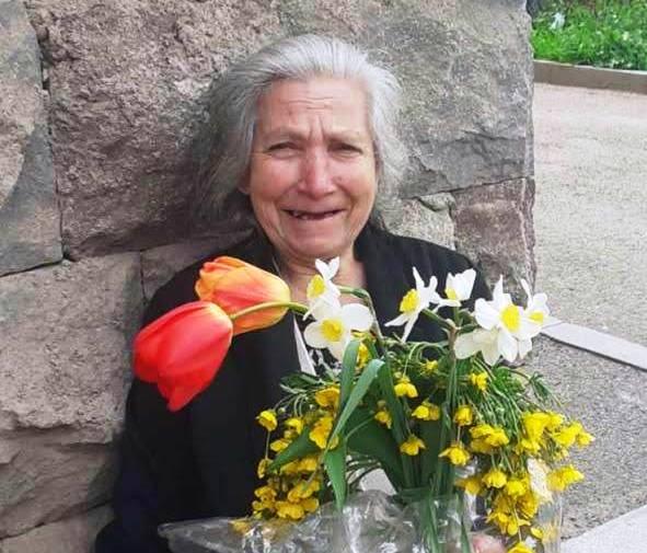 Alte Frau hält einen Strauß Blumen
