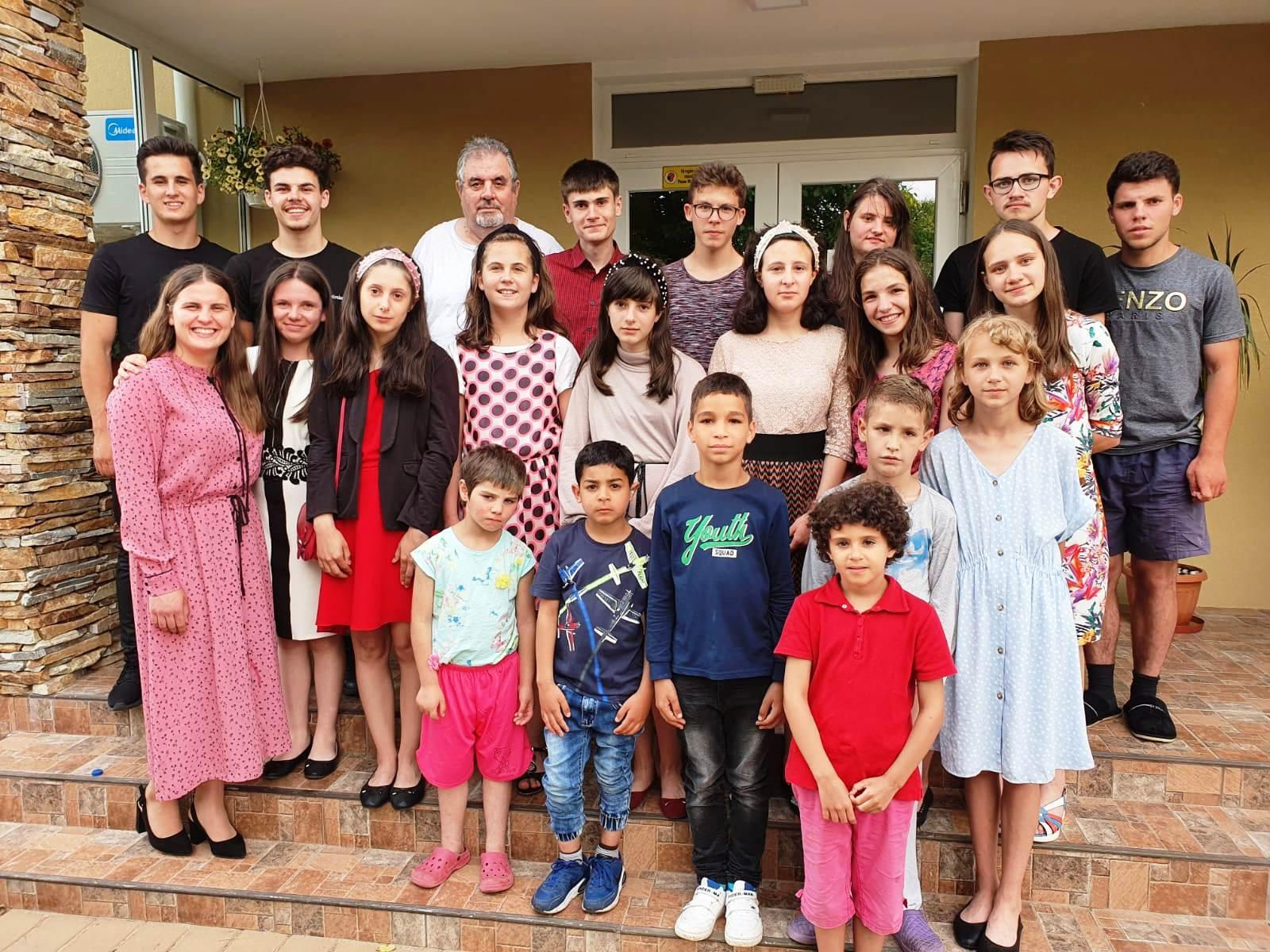 21 Kinder und Jugendliche sowie ein älterer Mann stehen auf den Treppenstufen vor einem Gebäude