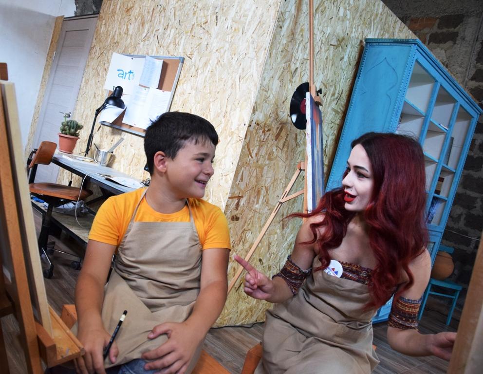 Ein Junge und eine junge Frau unterhalten sich; der Junge hält einen Stift in der Hand, links neben ihm steht eine Staffelei