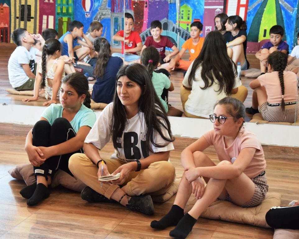 Zwei Mädchen sitzen rechts und links von einer Betreuerin auf dem Boden einer Halle; im großen Spiegel hinter ihnen sieht man noch mehr Kinder, die im Kreis sitzen
