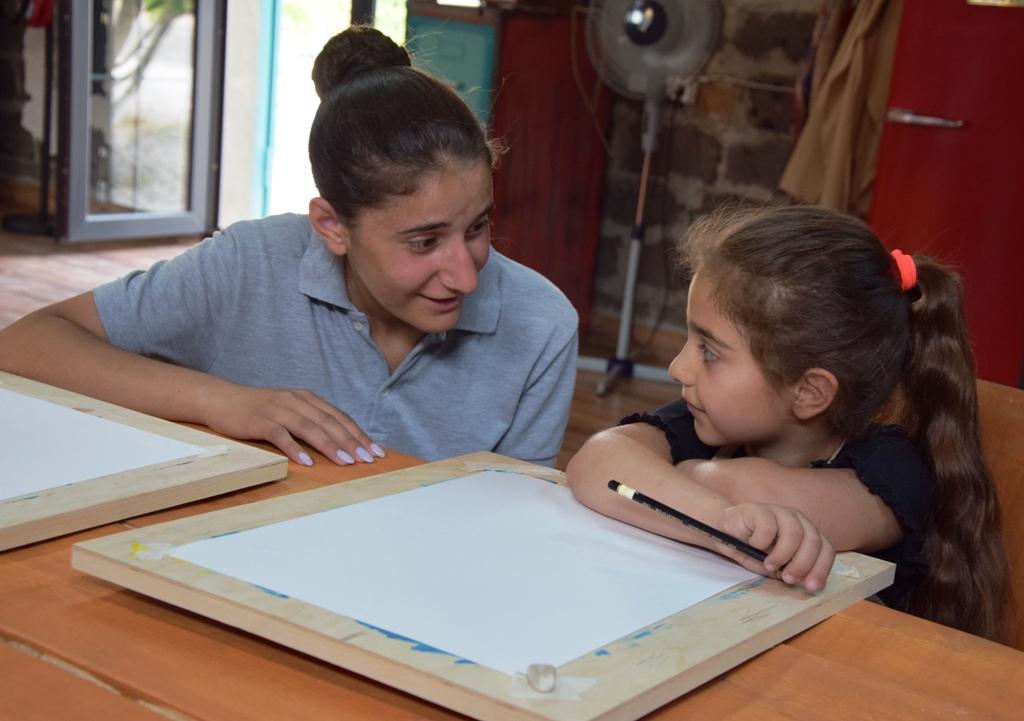 Ein Mädchen und eine junge Frau unterhalten sich; vor ihnen liegen zwei weiße Leinwände