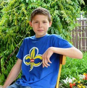 Dunkelblonder Junge im blauen T-Shirt mit Aufdruck sitzt auf einem Stuhl vor einem Strauch