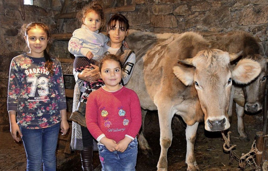Eine Frau und drei Mädchen im Stall mit einer Kuh