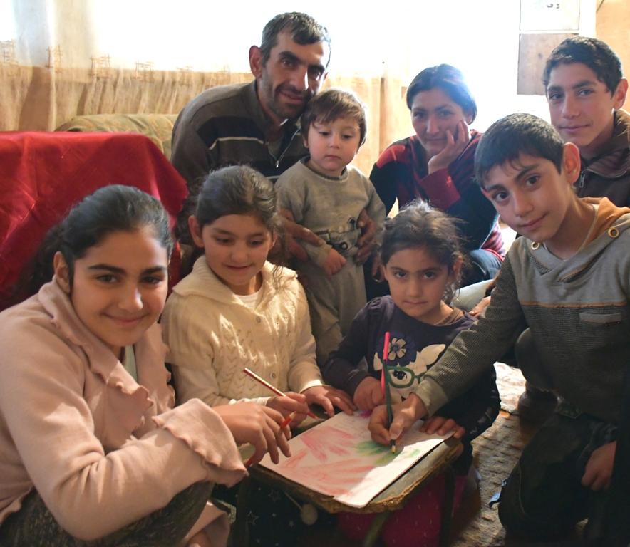 Eine Familie sitzt um einen selbst gestalteten Brief