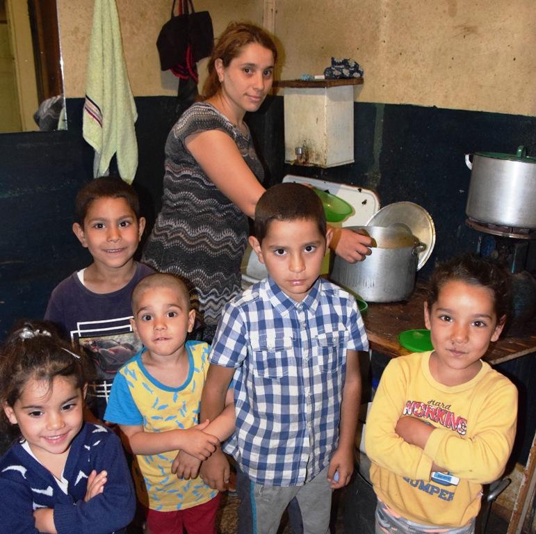 Eine Frau mit fünf kleinen Kindern steht in einer maroden Küche