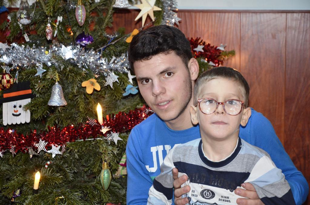 Ein Jugendlicher sitzt vor einem Weihnachtsbaum und hält einen kleineren Jungen mit Brille auf dem Schoß