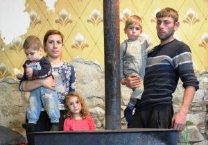 Vater, Mutter, zwei Söhne und eine Tochter stehen hinter einem Ofen