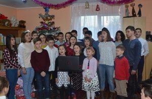 Singende Kinder vor einem Weihnachtsbaum in einem geschmückten Zimmer