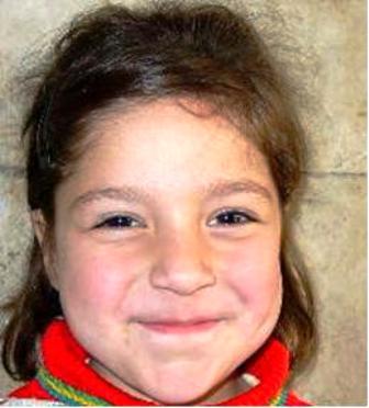 Kleines dunkelblondes Mädchen lächelt in die Kamera