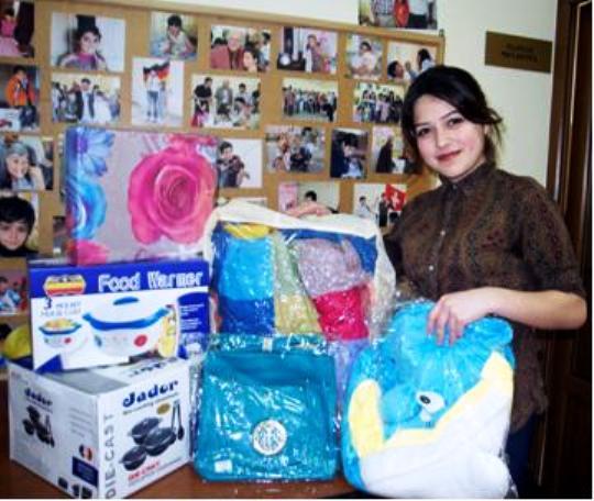 Eine junge Frau steht an einem Tisch mit vielen Geschenken