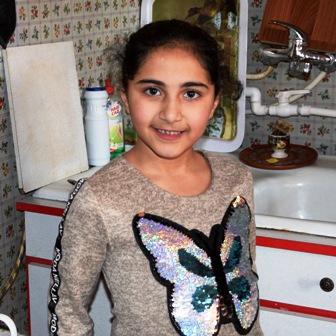 Dunkelhaariges Mädchen in hellem Pulli mit Schmetterlingsaufnäher steht in einer Küche